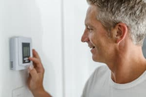 Man smiling at thermostat due to heating tune up
