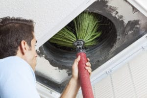 Technician performs home duct cleaning