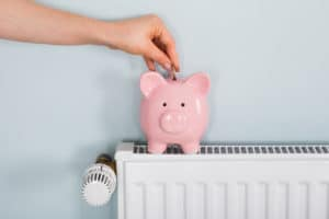 Piggy bank on radiator shows savings of replacing boiler