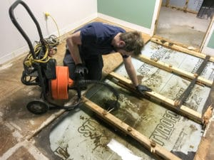 Plumber repairs a basement sewer emergency