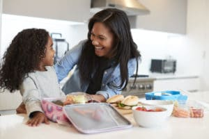 Daughter and mother preparing a back to school lunch in kitchen