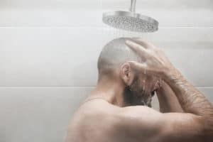 Man in shower enjoys plenty of hot water from the water heater.