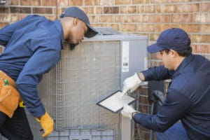 HVAC technicians inspect a system that uses freon