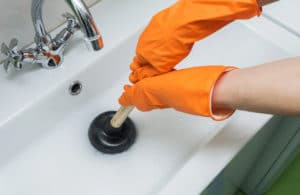 Person uses a plunger to fix a plumbing problem