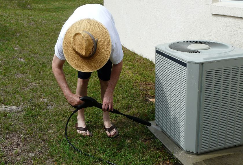 homeowner cleaning outside air conditioning unit